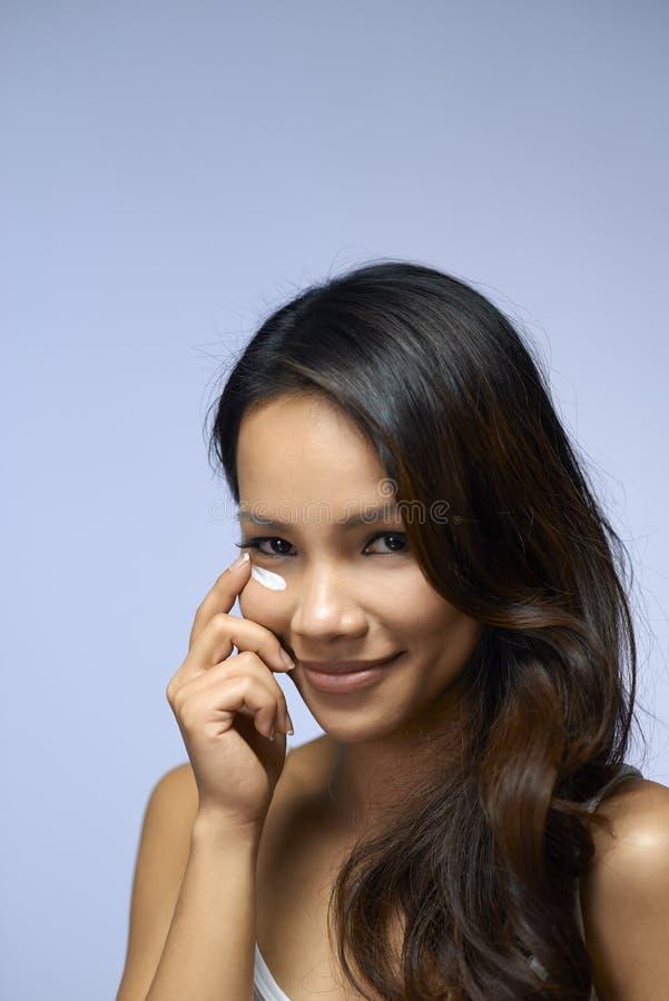 Fille asiatique employant la crème et des cosmétiques de beauté photographie stock