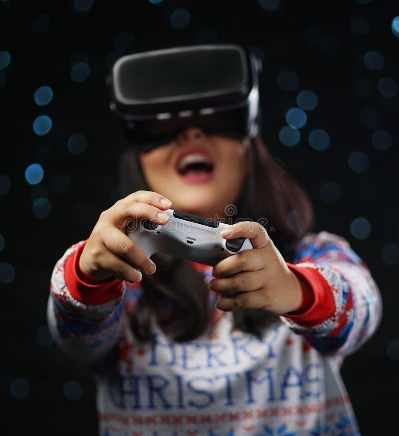 Fille asiatique enthousiaste jouant des jeux vidéo avec l'obscurité de réalité virtuelle image libre de droits