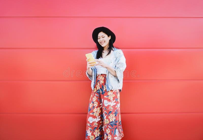 Fille asiatique heureuse à l'aide du téléphone portable extérieur - influencer social chinois ayant l'amusement avec de nouveaux  photo stock