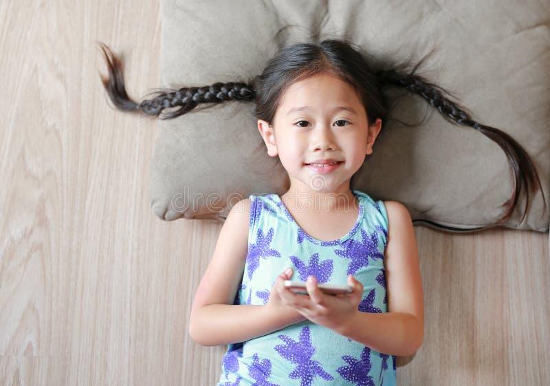 Fille asiatique heureuse d'enfant jouant le smartphone se trouvant sur le plancher en bois Vue supérieure photographie stock