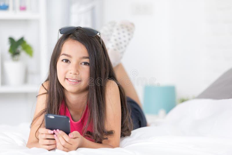 Fille asiatique heureuse lisant le téléphone intelligent avec le visage de sourire sur le lit photographie stock libre de droits