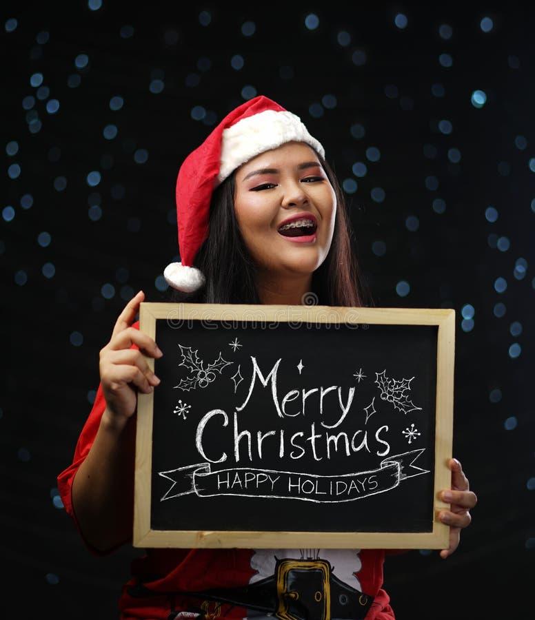 Fille asiatique heureuse portant Santa Costume Christmas Holding Merry C photos stock