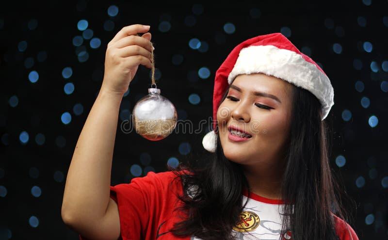 Fille asiatique heureuse portant Santa Costume Holding Christmas Bauble images libres de droits
