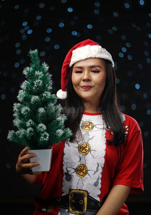 Fille asiatique heureuse portant Santa Costume Holding Small Christmas T photographie stock