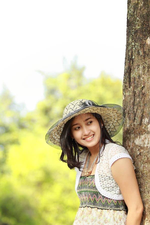 Fille asiatique heureuse souriant en stationnement photographie stock