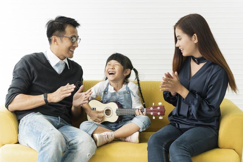 Fille asiatique jouant la guitare et chantant avec le père et la mère images stock