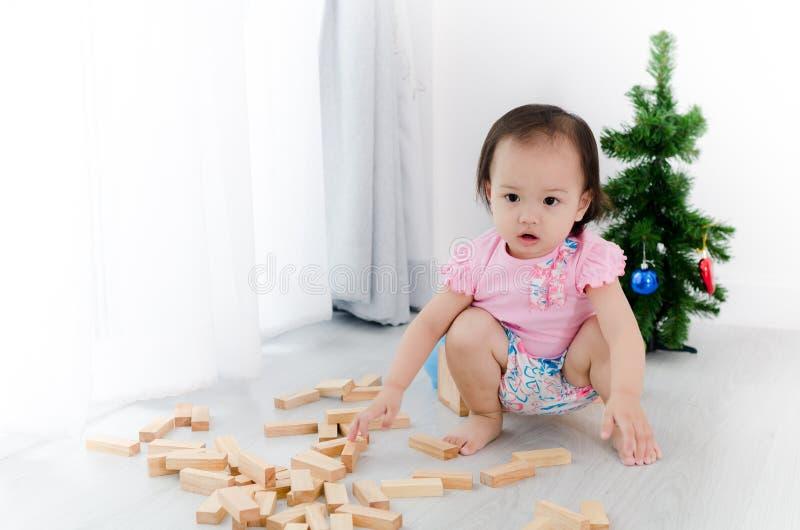 Fille asiatique jouant le bloc en bois sur le plancher avec l'arbre de Noël photo libre de droits