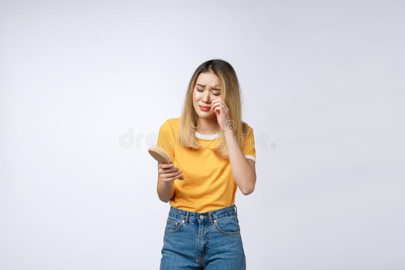 Fille asiatique malheureuse au téléphone, téléphone parlant de femme asiatique fâchée avec son ami, d'isolement sur le fond blanc photographie stock