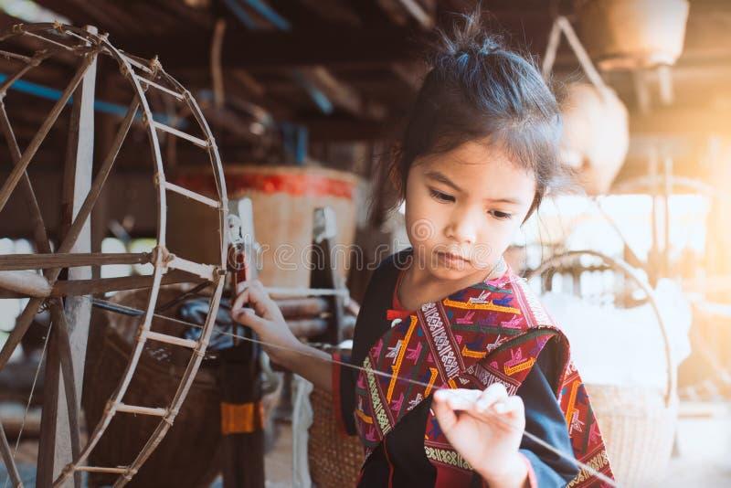 Fille asiatique mignonne d'enfant à l'aide de la roue de rotation en bois traditionnelle photographie stock libre de droits