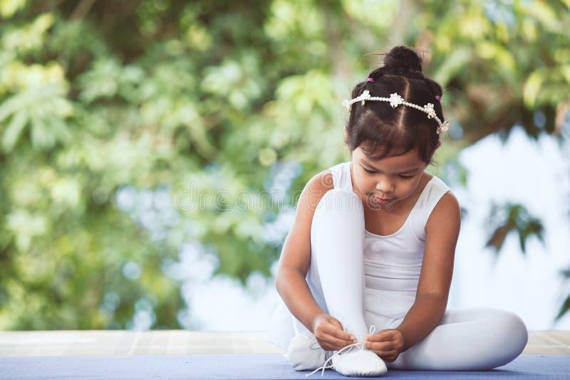 Fille asiatique mignonne d'enfant attachant sur des chaussures de pointe de pieds photographie stock libre de droits