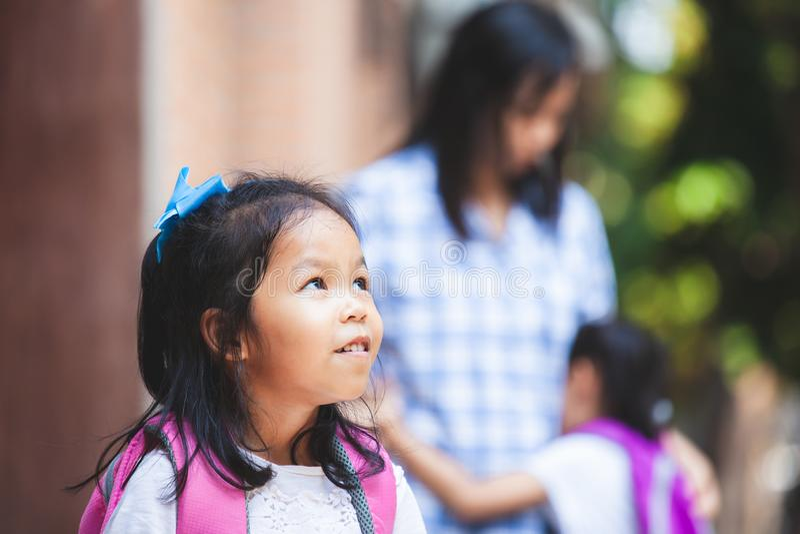 Fille asiatique mignonne d'enfant attendant sa soeur pour aller instruire ensemble après étreinte leur mère photos libres de droits