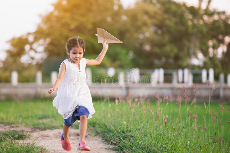 Fille asiatique mignonne d'enfant courant et jouant l'avion de papier de jouet photos stock