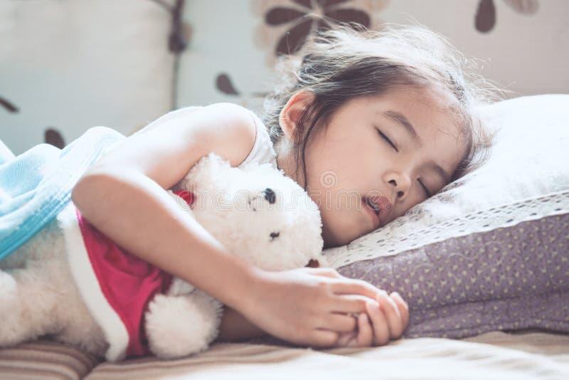 Fille asiatique mignonne d'enfant dormant et étreignant son ours de nounours image libre de droits