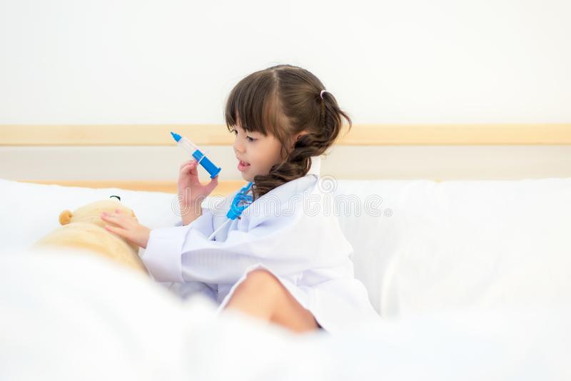 Fille asiatique mignonne d'enfant jouant le docteur avec le jouet de peluche à la maison photo stock