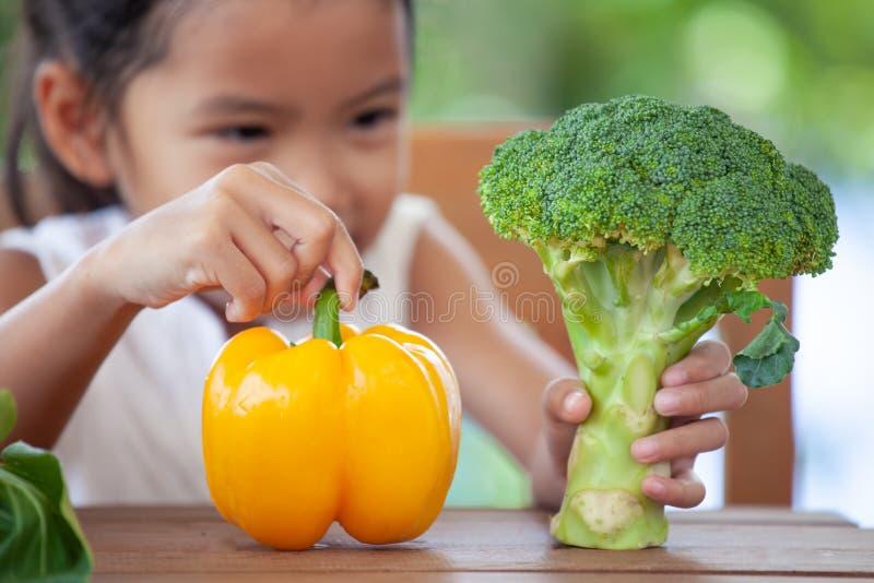 Fille asiatique mignonne d'enfant se renseignant sur des légumes images stock