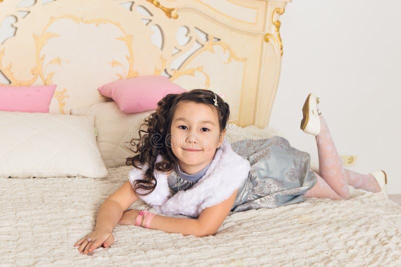 Fille asiatique mignonne d'enfant se trouvant sur le lit blanc photo stock