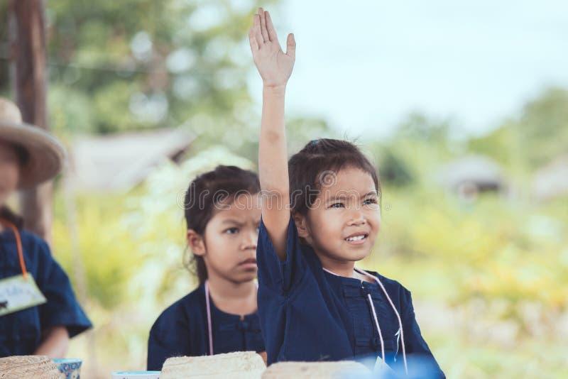 Fille asiatique mignonne d'enfant soulevant sa main dans le ciel à la réponse image stock