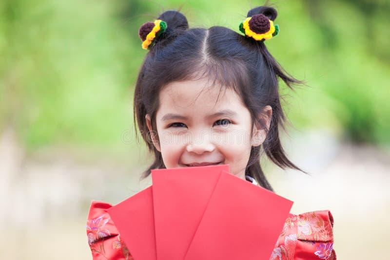 Fille asiatique mignonne d'enfant tenant l'enveloppe rouge photographie stock