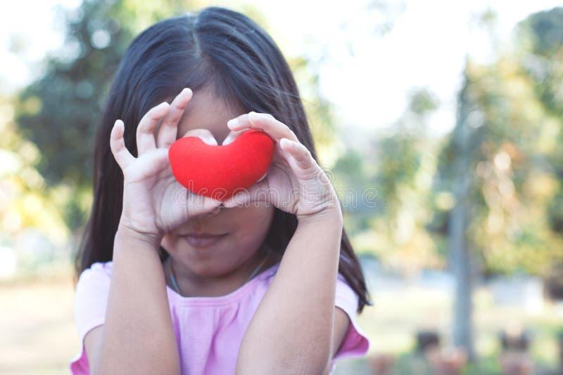 Fille asiatique mignonne de petit enfant avec le coeur rouge sur les yeux photo libre de droits