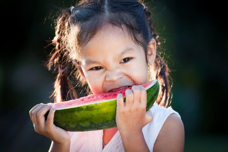 Fille asiatique mignonne de petit enfant mangeant du fruit frais de pastèque photo stock