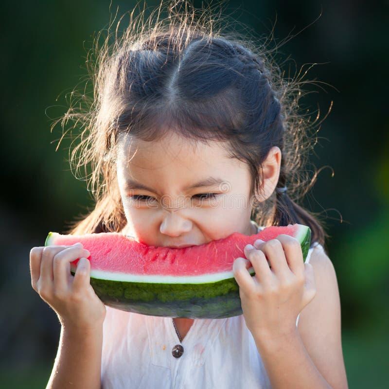 Fille asiatique mignonne de petit enfant mangeant du fruit frais de pastèque image stock
