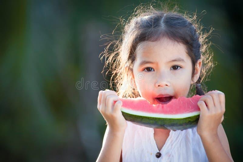 Fille asiatique mignonne de petit enfant mangeant du fruit frais de pastèque image libre de droits
