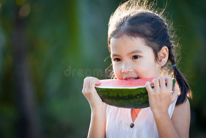 Fille asiatique mignonne de petit enfant mangeant du fruit frais de pastèque photographie stock