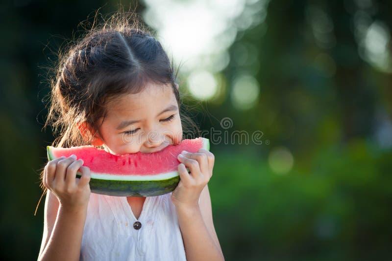 Fille asiatique mignonne de petit enfant mangeant du fruit frais de pastèque photo libre de droits