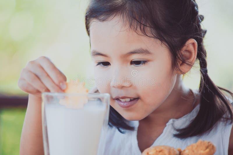 Fille asiatique mignonne de petit enfant mangeant le biscuit avec du lait image stock