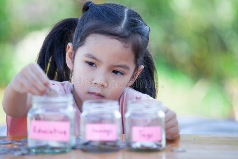 Fille asiatique mignonne de petit enfant mettant la pièce de monnaie dans la bouteille en verre photographie stock