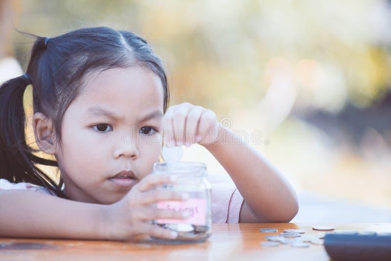 Fille asiatique mignonne de petit enfant mettant la pièce de monnaie dans la bouteille en verre photos stock