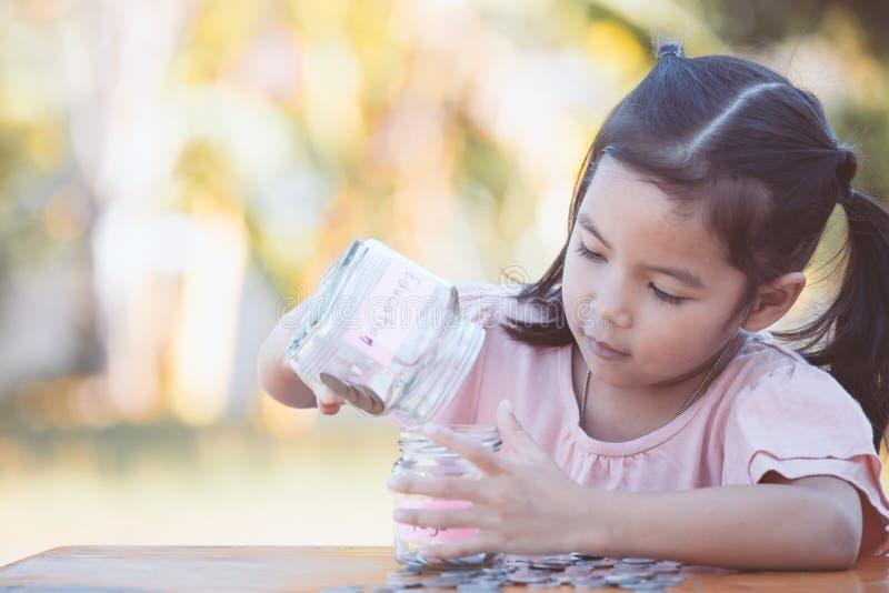 Fille asiatique mignonne de petit enfant mettant la pièce de monnaie dans la bouteille en verre photos libres de droits