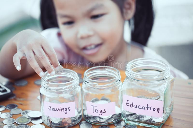 Fille asiatique mignonne de petit enfant mettant la pièce de monnaie dans la bouteille en verre photo stock