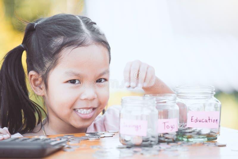 Fille asiatique mignonne de petit enfant mettant la pièce de monnaie dans la bouteille en verre image stock