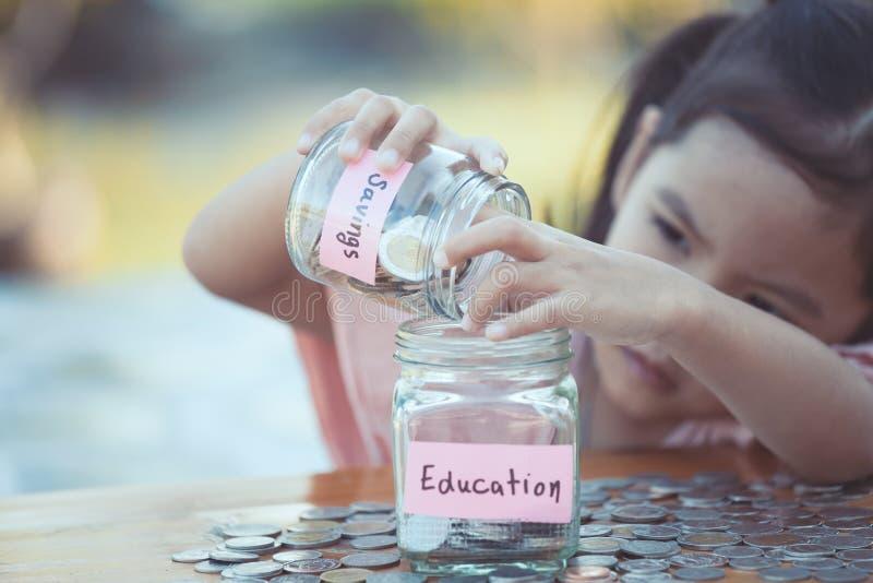 Fille asiatique mignonne de petit enfant mettant la pièce de monnaie dans la bouteille en verre images stock