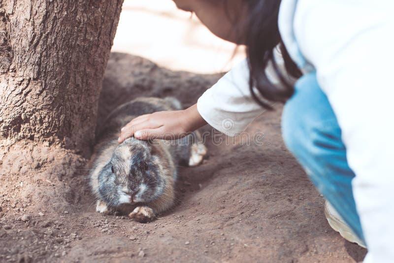 Fille asiatique mignonne de petit enfant touchant et jouant avec le lapin images stock