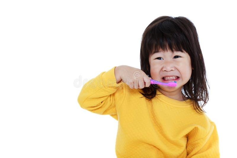 Fille asiatique mignonne de plan rapproché avec une brosse à dents à disposition allant balayer photos libres de droits