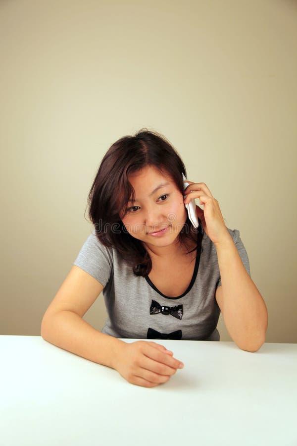 Fille asiatique mignonne faisant un appel image stock