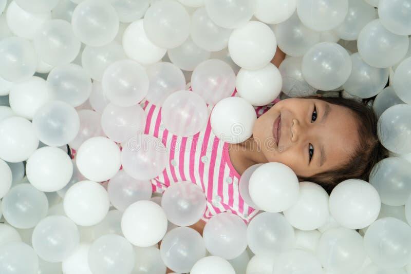 Fille asiatique mignonne heureuse d'enfant ayant l'amusement à jouer avec les boules en plastique blanches images stock