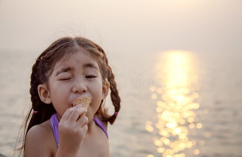 Fille asiatique mignonne mangeant la crème glacée avec le coucher du soleil photographie stock