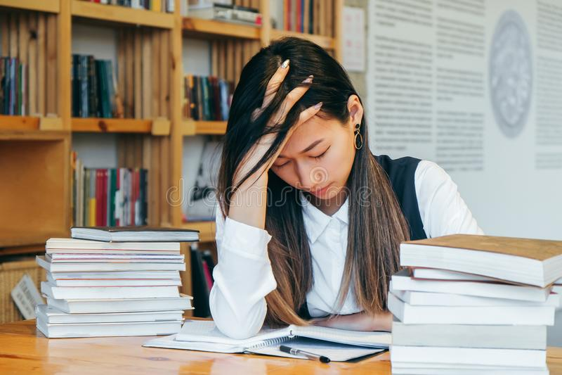 Fille asiatique mignonne s'asseyant dans une bibliothèque, entourée par des livres, pensant à l'étude L'étudiant de l'adolescence images stock