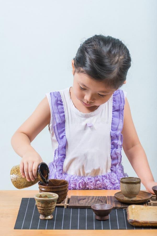 Fille asiatique mignonne tout en jouant une tasse de thé et une tasse de saké dessus photographie stock