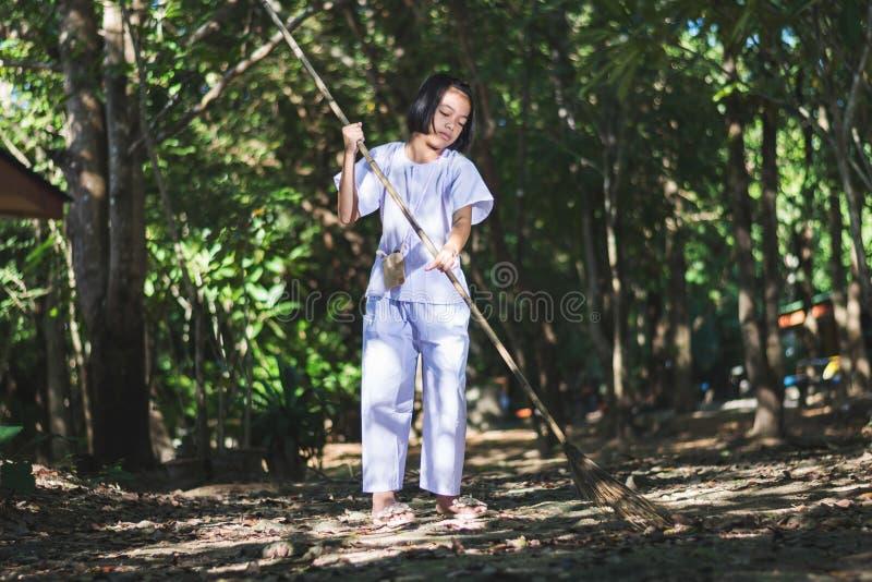 Fille asiatique nettoyant le secteur du temple dans la forêt, acte volontaire photo libre de droits