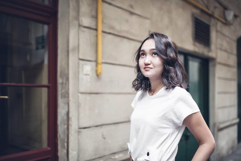 Fille asiatique optimiste dans un T-shirt blanc, recherchant photographie stock