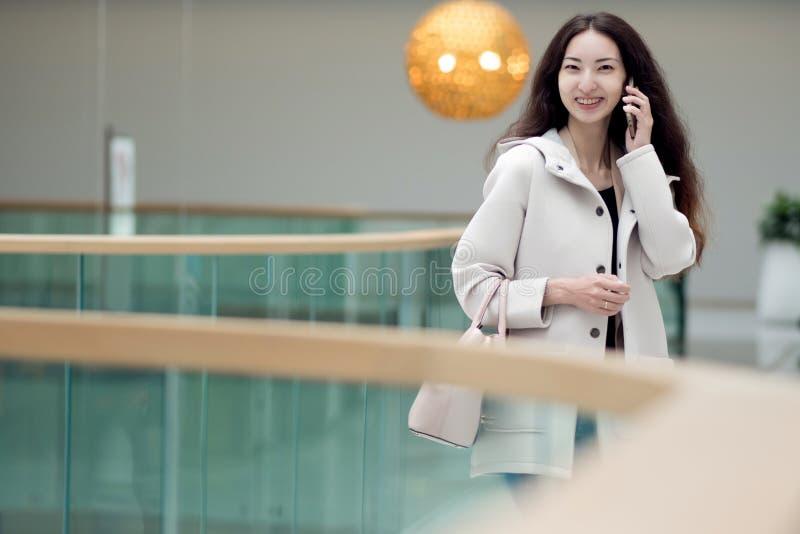 Fille asiatique parlant au téléphone, centre commercial images libres de droits