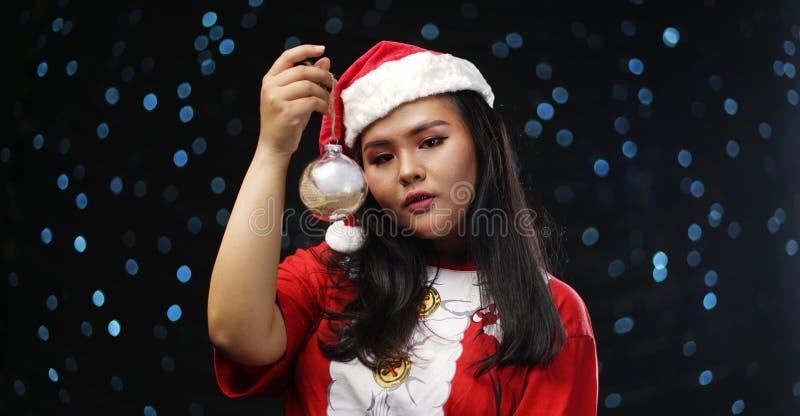 Fille asiatique portant Santa Costume Holding Christmas Bauble image libre de droits