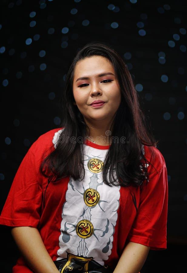 Fille asiatique portant Santa Shirt Christmas Dark Glow Bokeh Backgro image stock