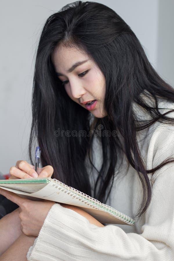 Fille asiatique prenant des notes image stock