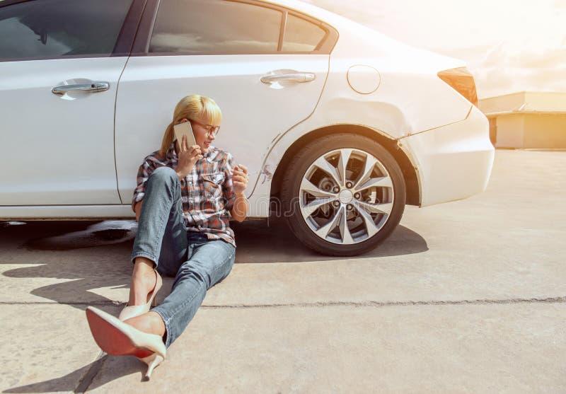 Fille asiatique s'asseyant près de sa voiture et entretien photos stock