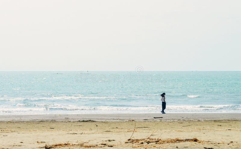 Fille asiatique simple marchant le long de la côte photo stock